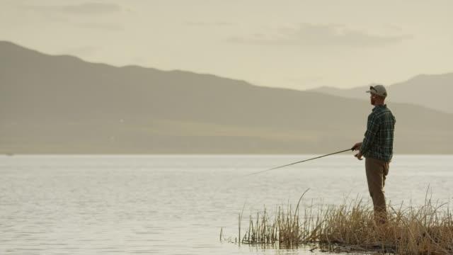 Wide panning shot of man fly fishing at lake / Vineyard, Utah, United States
