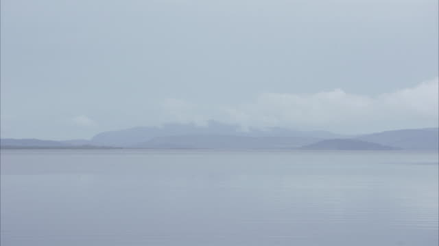 Wide panning shot of misty lake and mountains