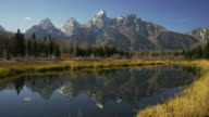 Wide panning shot of mountain reflection in river / Grand Teton National Park, Wyoming, United States