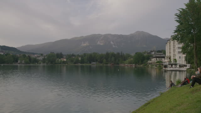 Wide panning shot of people relaxing at lake / Bled, Slovenia