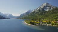 Wide panning shot of river near mountains / Waterton Lake, Alberta, Canada