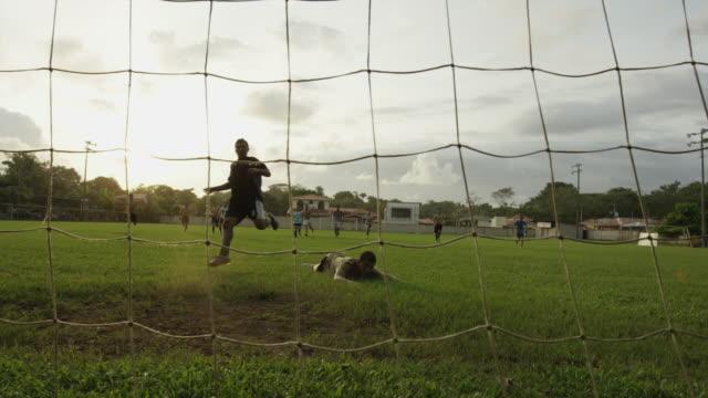 Wide panning shot of soccer player scoring goal in net / Esterillos, Puntarenas, Costa Rica