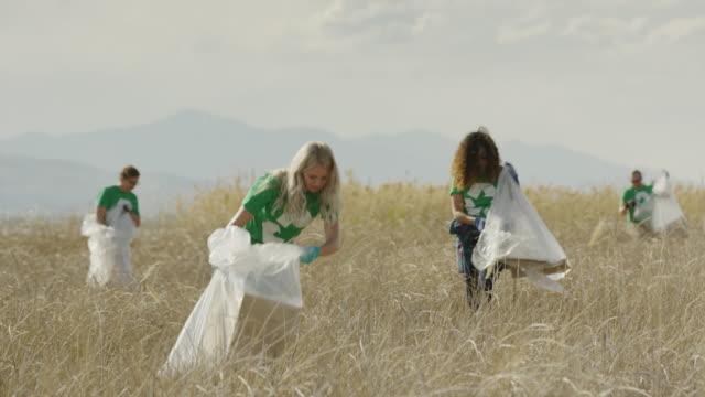 Wide panning shot of volunteers collecting garbage in field / Vineyard, Utah, United States