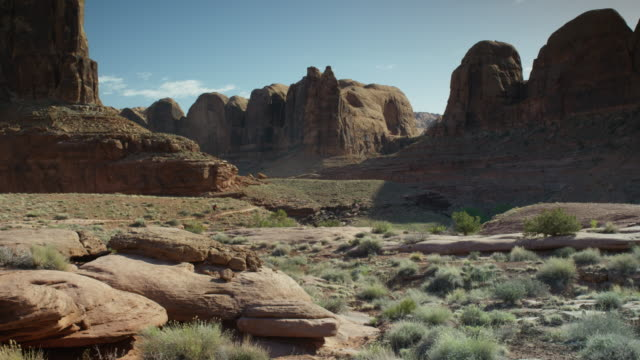 Wide panning shot of woman riding bicycle in mountains / Moab, Utah, United States