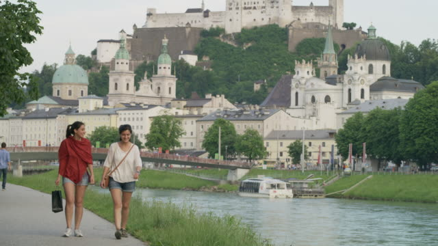 Wide panning shot of women walking near river / Salzburg, Austria