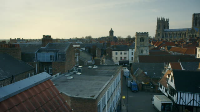 Wide panning shot over York's rooftops towards the cathedral of York Minster, York, UK.