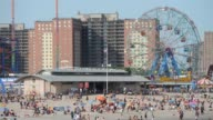 A wide scenic shot of a crowded beach Cyclone Wonder Wheel and housing projects on a clear sunny day in Coney Island New York A wide scenic shot of a...