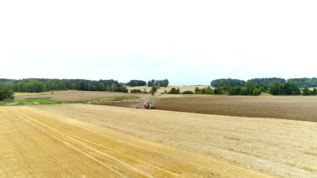 Wide shoot of tractor working on agricultural field.