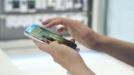 Wide shot a customer tries out a Samsung Electronics Co Galaxy S6 Edge smartphone on display at the company's Galaxy Zone showroom in Seoul Medium...