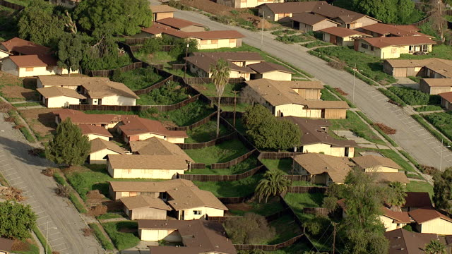 Wide Shot aerial tracking-left - Abandoned homes fill a Los Angeles suburb. / Los Angeles, California, USA