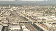 Wide Shot aerial tracking-left - Bridges span the LA River in an industrial area. / Los Angeles, California, USA