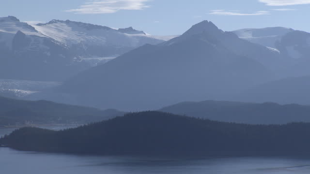 'Wide Shot aerial tracking-right-A blue mist hovers over massive Alaskan mountains and a river. / Alaska, USA'