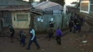 Wide shot African school children walking in Kenyan streets