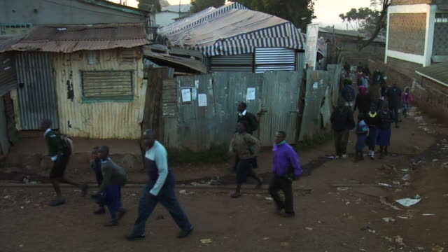 Wide shot African school children walking in Kenyan streets