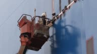 Wide shot an employee standing on an elevated platform moves the platform towards a ship under construction Medium shot an employee standing on an...