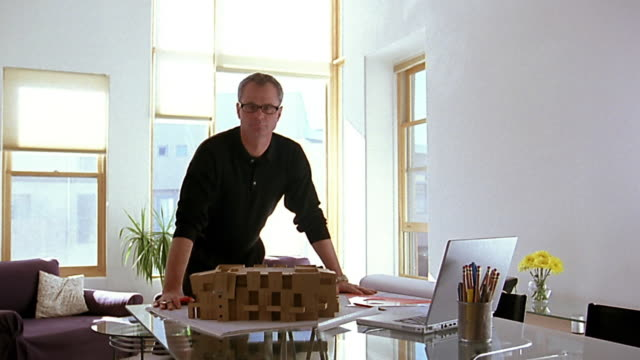 Wide shot architect posing at table behind model of building