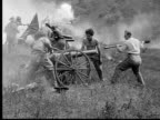1913 REENACTMENT B/W Wide shot Army officers and soldiers loading and firing cannons on battlefield during Civil War battle reenactment / USA