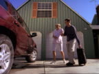 wide shot as a young expectant couple walks out of their house and into their car to travel to the hospital