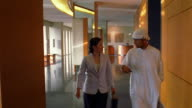 Wide shot Asian businesswoman & Middle Eastern businessman in Muslim clothing talk in hallway after meeting