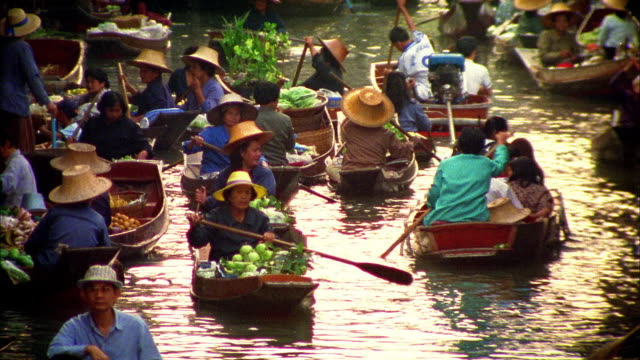 Wide shot Asian women paddling boats loaded with food on floating market / Damneon Saduak, Thailand