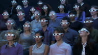 Wide shot audience wearing 3-D glasses reacting to movie out of frame with shock and pleasure
