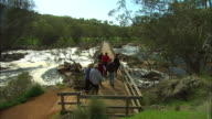 wide shot Avon River group of mature bushwalker tourists with Aboriginal guides pass along bush track beside river / walkers cross low wooden...