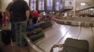 Wide shot baggage on carousel with people waiting / Hartsfield Airport, Atlanta