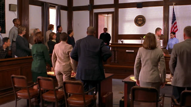 Wide shot bailiff announcing judge / people standing up / judge entering courtroom / people sitting down