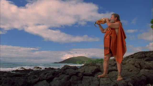 Wide shot bearded man blowing large shell / coastline in background
