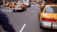 Wide shot bike messenger avoiding being hit by taxi door opening into traffic / NYC