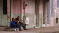 Wide shot Black man playing trumpet & boy playing trombone on street corner / New Orleans