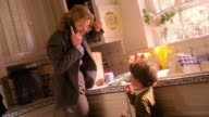 CANTED wide shot blonde businesswoman on telephone talking to small boy eating cookie in kitchen