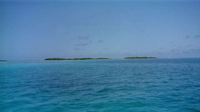 Wide shot boat point of view expanse of ocean approaching island in the distance / Los Roques Island, Venezuela