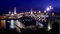 Wide shot boats passing under Pont de Alexandre III on River Seine at night / Paris, France