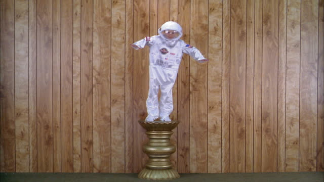Wide shot boy in astronaut space suit costume posing on pedestal w/wood paneling in background