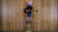 Wide shot boy in rock star costume standing w/electric guitar on pedestal