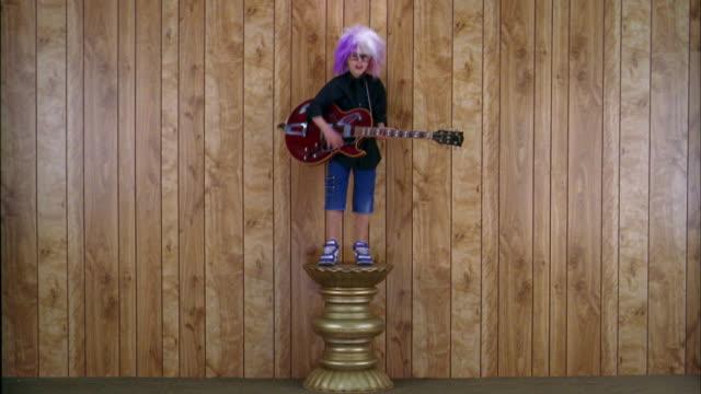Wide shot boy in rock star costume standing w/electric guitar on pedestal