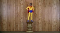 Wide shot boy in super hero costume posing on pedestal w/wood paneling in background
