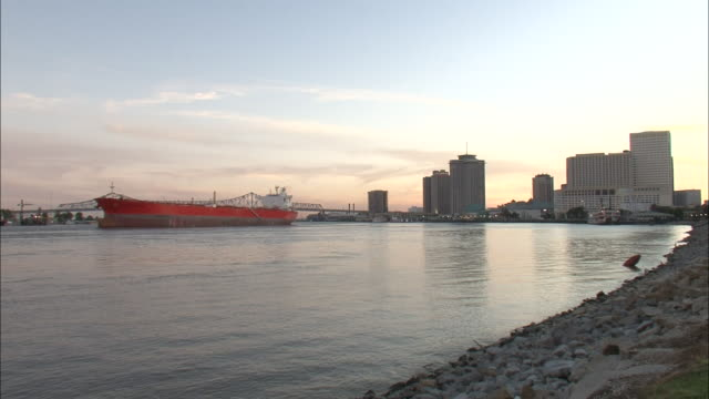 Wide Shot - Bridge, river, boat, and buildings along coastline at sunset / New Orleans Louisiana