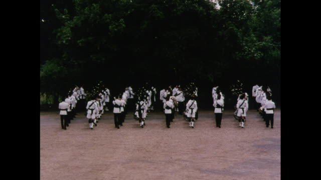 Wide Shot Brigade of Gurkhas playing bagpipes and marching in Scotland / United Kingdom