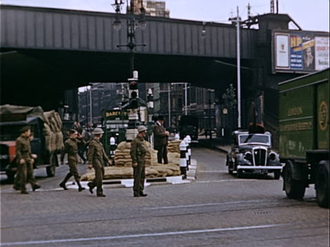 Wide shot British soldiers walking past sandbags piled in heap in street median during war preparations / London England