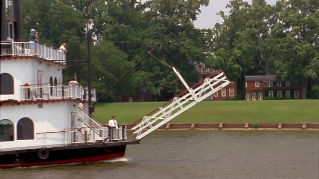 Wide shot building with brick facade on riverbank / dolly shot riverboat 'Annabel Lee' passing on river / Baltimore