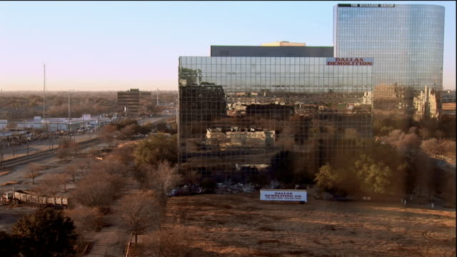 Wide shot building with mirrored windows being demolished / cloud of smoke from imploding building