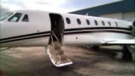 Wide shot Businessman exiting private jet and waving at Opa Locka Airport/ Miami, Florida, USA