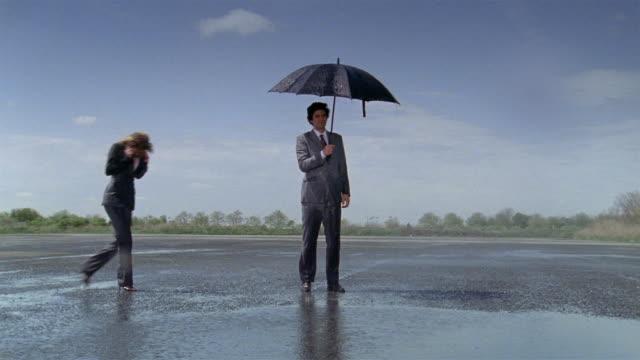 Wide shot businessman holding umbrella during rain storm in parking lot / women joining him under umbrella