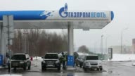 Wide shot cars parked by fuel pumps at a gas station operated by OAO Gazprom Neft in Moscow Russia on Wednesday Feb 12 A fuel pump attendant serves a...