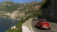 Wide shot cars rounding coastal road with hillside town of Positano in background / Amalfi Coast, Campania, Italy