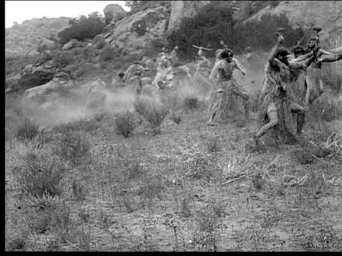 1914 B/W Wide shot Cavemen fighting each other in field with weapons