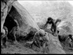 1914 B/W Wide shot Cavemen with weapons attacking unarmed cavemen outside cave entrance