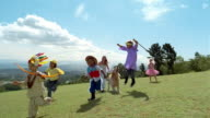 Wide shot children in costumes running across field/ low angle children and dog leaping/ Somerset West, South Africa